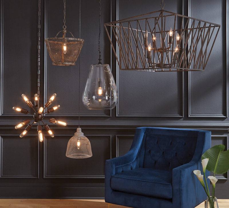 Five chandeliers and one blue velvet chair in a room
