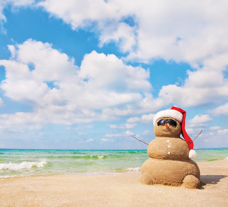 Sandman wearing Santa hat and sunglasses on beach