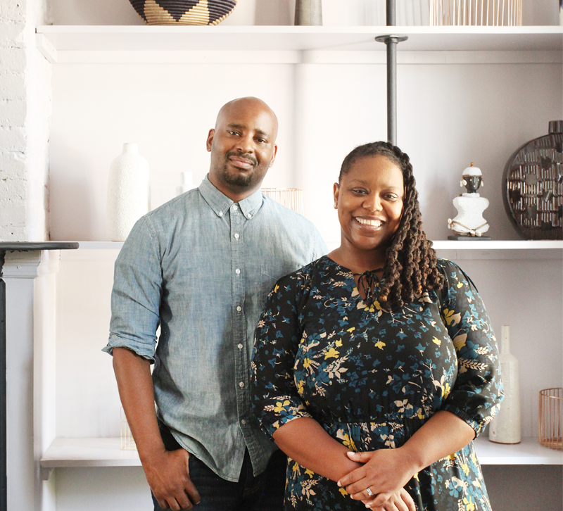 AphroChic designers Jeanine Hays and Bryan Mason stand together in front of bookcase