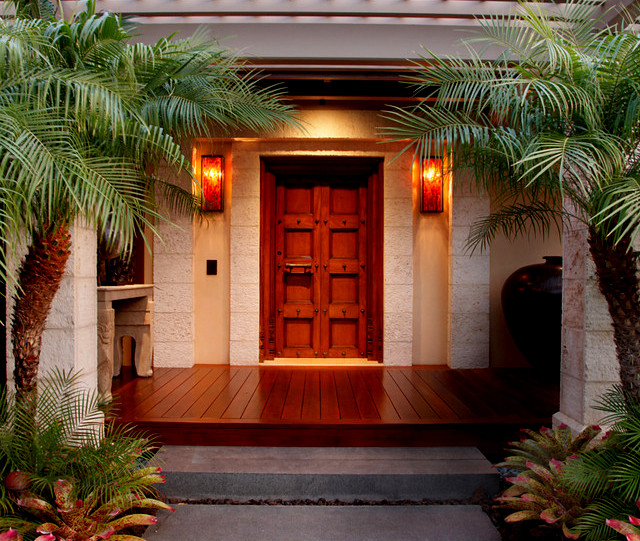 front door with sconces and palm trees