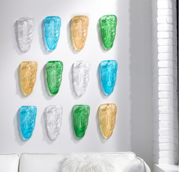 Amber, green, yellow and clear glass faces on wall from Phillips Collection