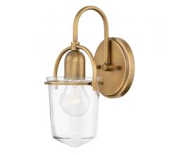 The Clancy wall sconce from Hinkley Lighting measures just 6 by 11.3 inche. Made of steel and clear glass, ideal for an Edison bulb. Available in five finishes, shown here in Heritage Brass. with Heritage brass backplate and arm and clear glass surrounding the bulb from Hinkley Lighting